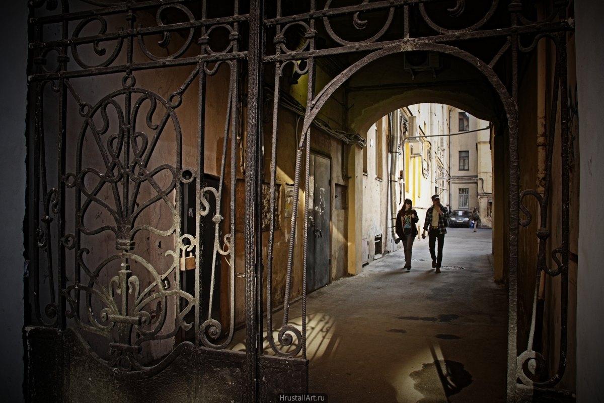 Мужчина и женщина идут по питерскому двору.