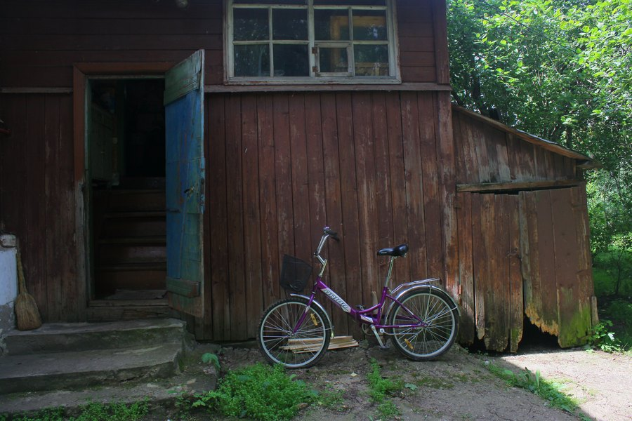У входа в старый дом стоит современный фиолетовый велик.