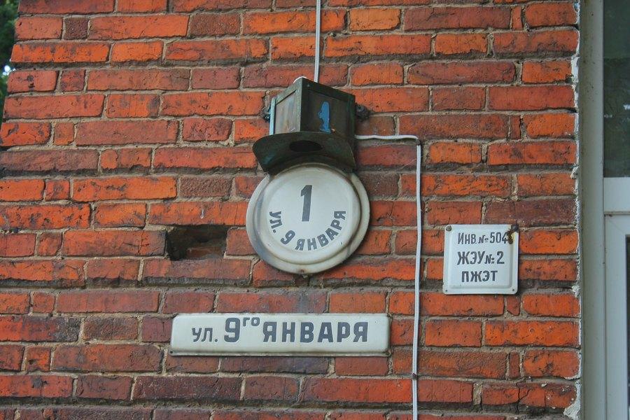 Стена красного кирпича с номером дома, названием улицы и инвентарным номером.
