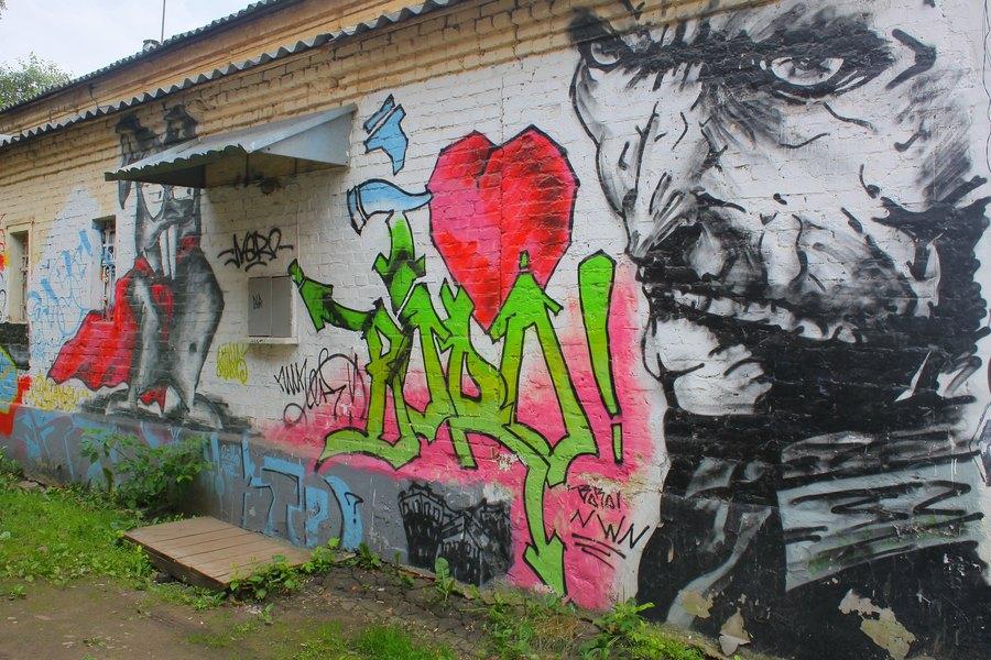 Низкая кирпичная стена с рисунком сумрачного лица, супер-хомяком и неясной надписью.