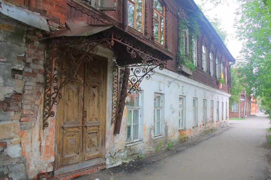 Первый этаж кирпичный, второй деревянный, козырёк крыльца украшен кованными завитками.