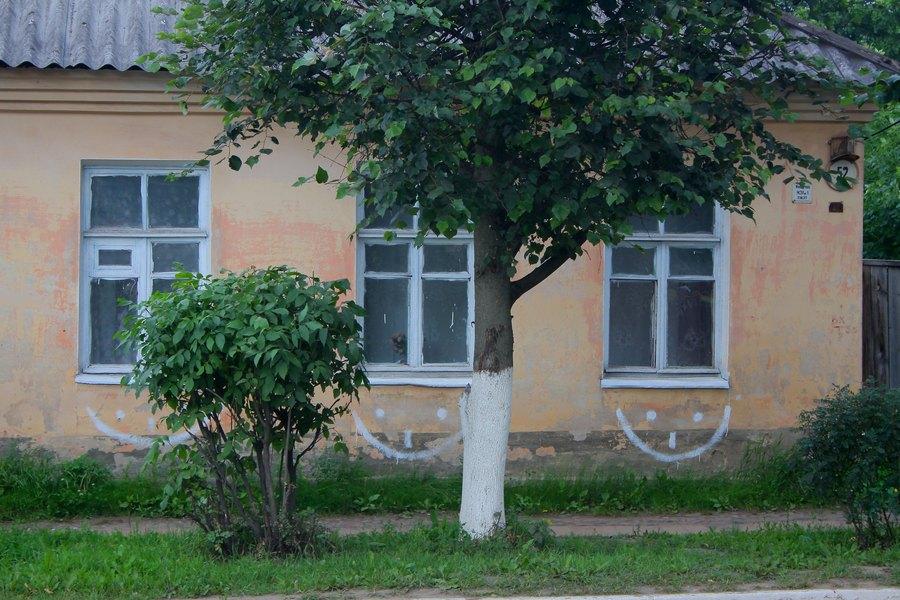 Скучный одноэтажный дом, под окнами нарисованы смайлы.