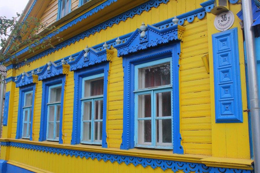 Богатая деревянная резьба на старом доме выкрашена в кислотные цвета: лимонный и голубой.