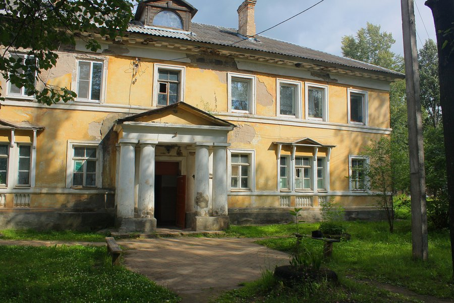 Обветшалый двухэтажный дом сталинской архитектуры. Крыльцо со сдвоенными колоннами.