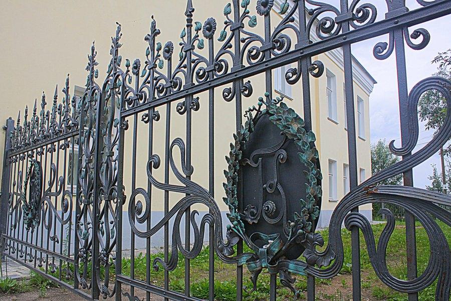 Красивые кованные ворота с вензелем и растительным орнаментом.