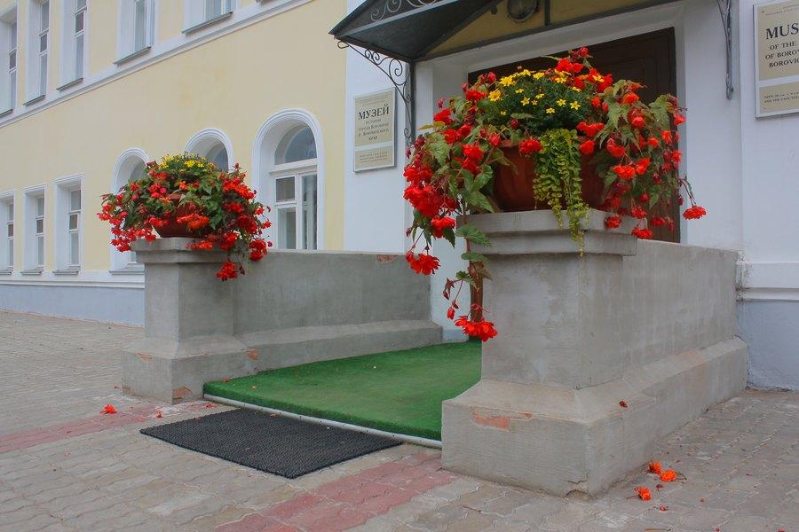 Крыльцо музея Боровичей, с большими вазонами и богатыми красными цветами.