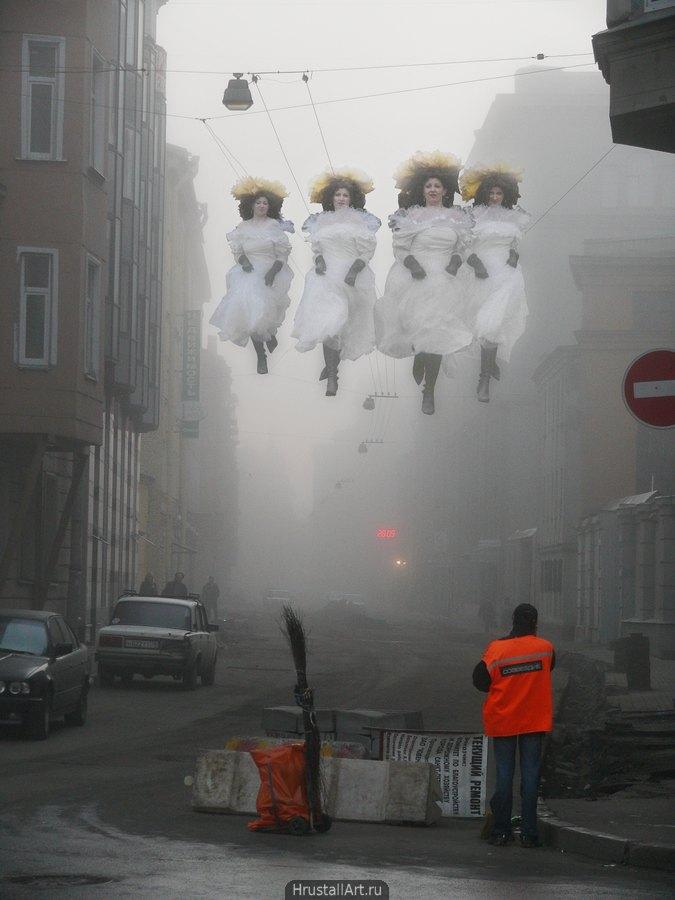 На перекрытой для ремонта питерской улице стоит дворник. Над улицей в утреннем тумане парят-скачут четверо девушек в старинном платье и венке осенних листьев.