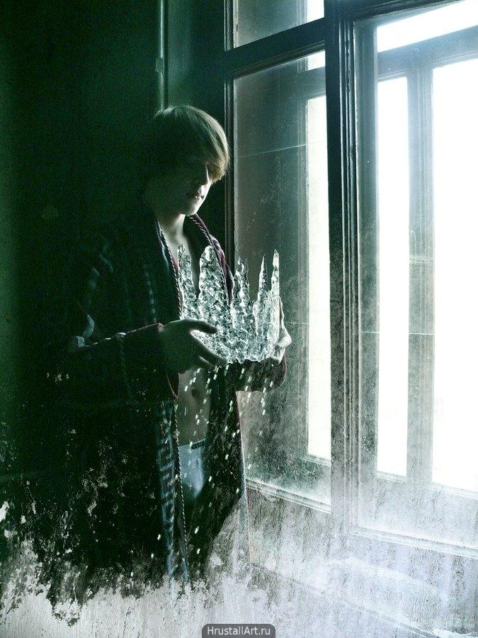 Молодой парень стоит у окна, он одет в халат, держит в руках ледяную корону, корона тает.