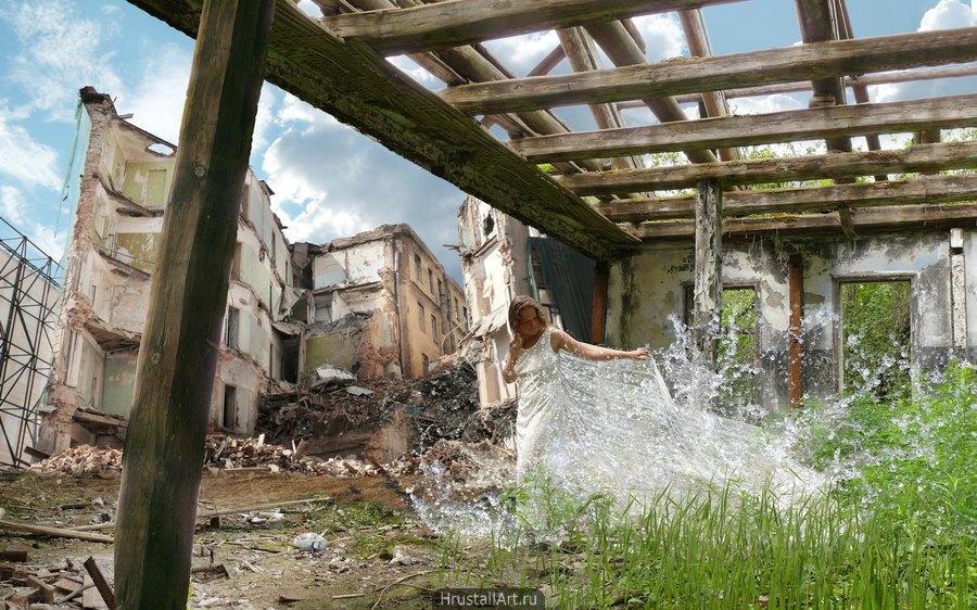 Руины домов, сквозь остовы идёт красивая девушка, она окружен брызгами воды, руины, которые она прошла зарастают буйной зеленью.