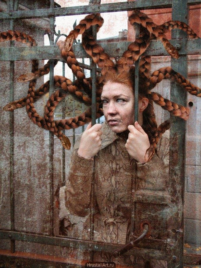 Пугающее лицо женщины с косами-змеями, она прислонилась к железной решётке.