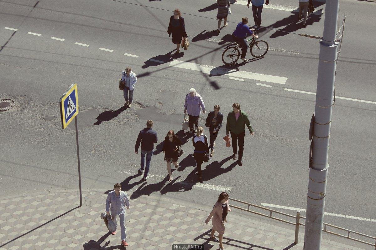 Пешеходный переход, вид сверху, два десятка людей под ярким летним солнцем спешат через дорогу.
