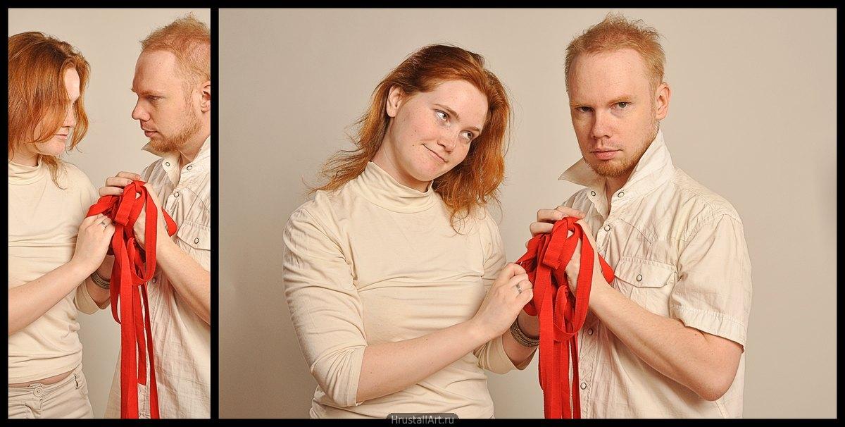 Парень смотрит вперёд, девушка смотрит на него с укором. Парень и девушка держат прижались друг к другу и держат вместе красные ленты.