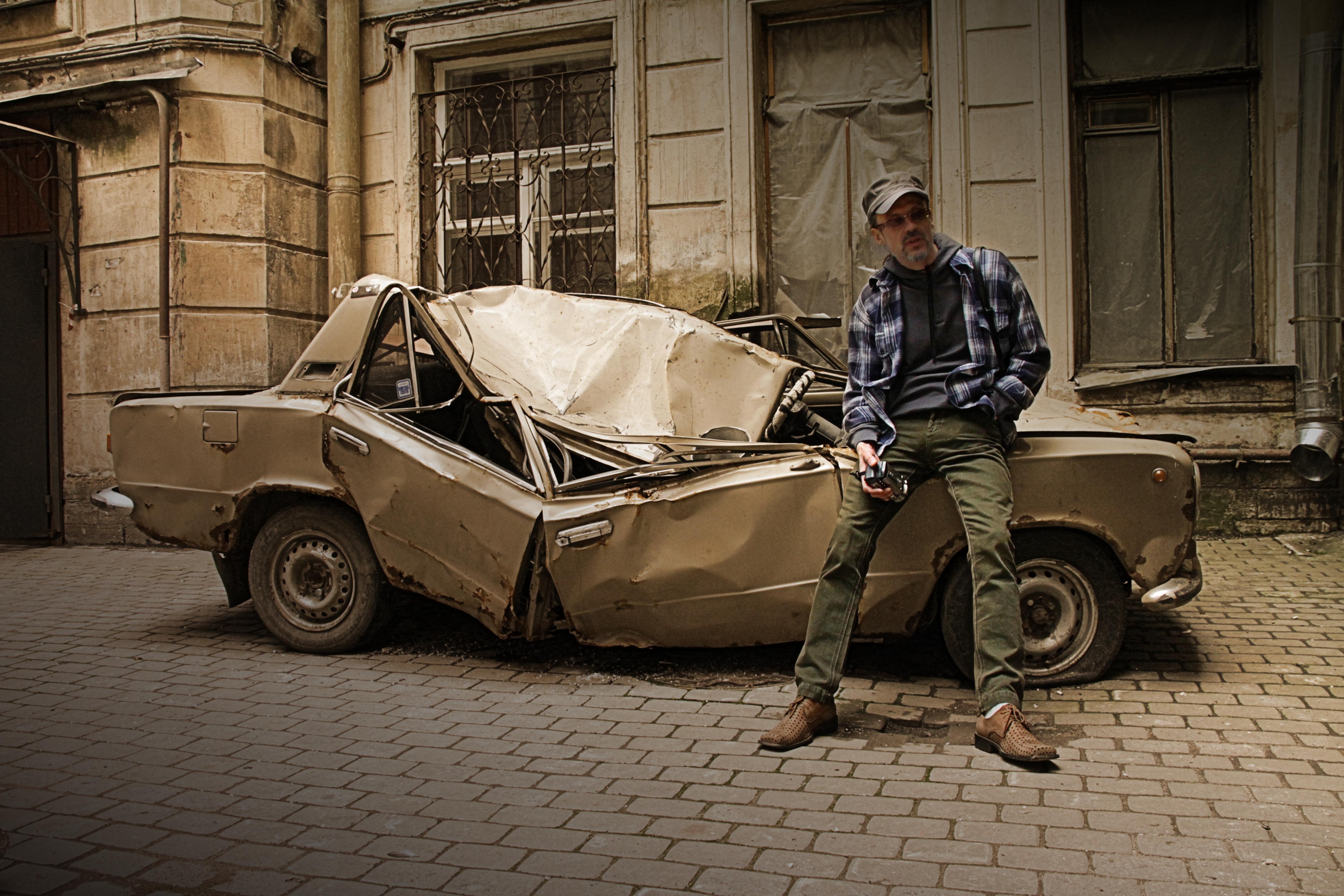Мужчина в питерском дворе прислонился к разбитой машине.