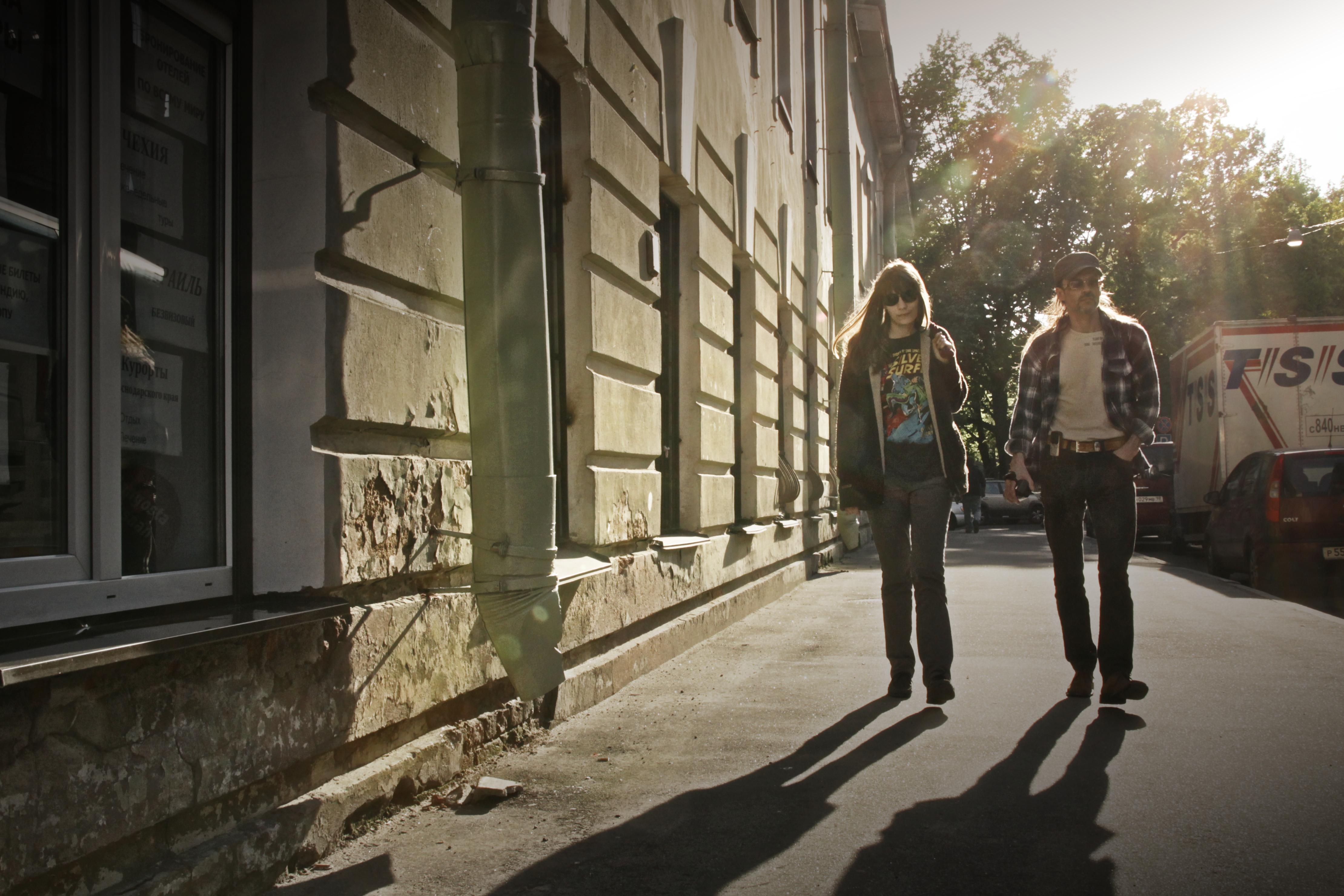Двое гуляют по вечерней улице.