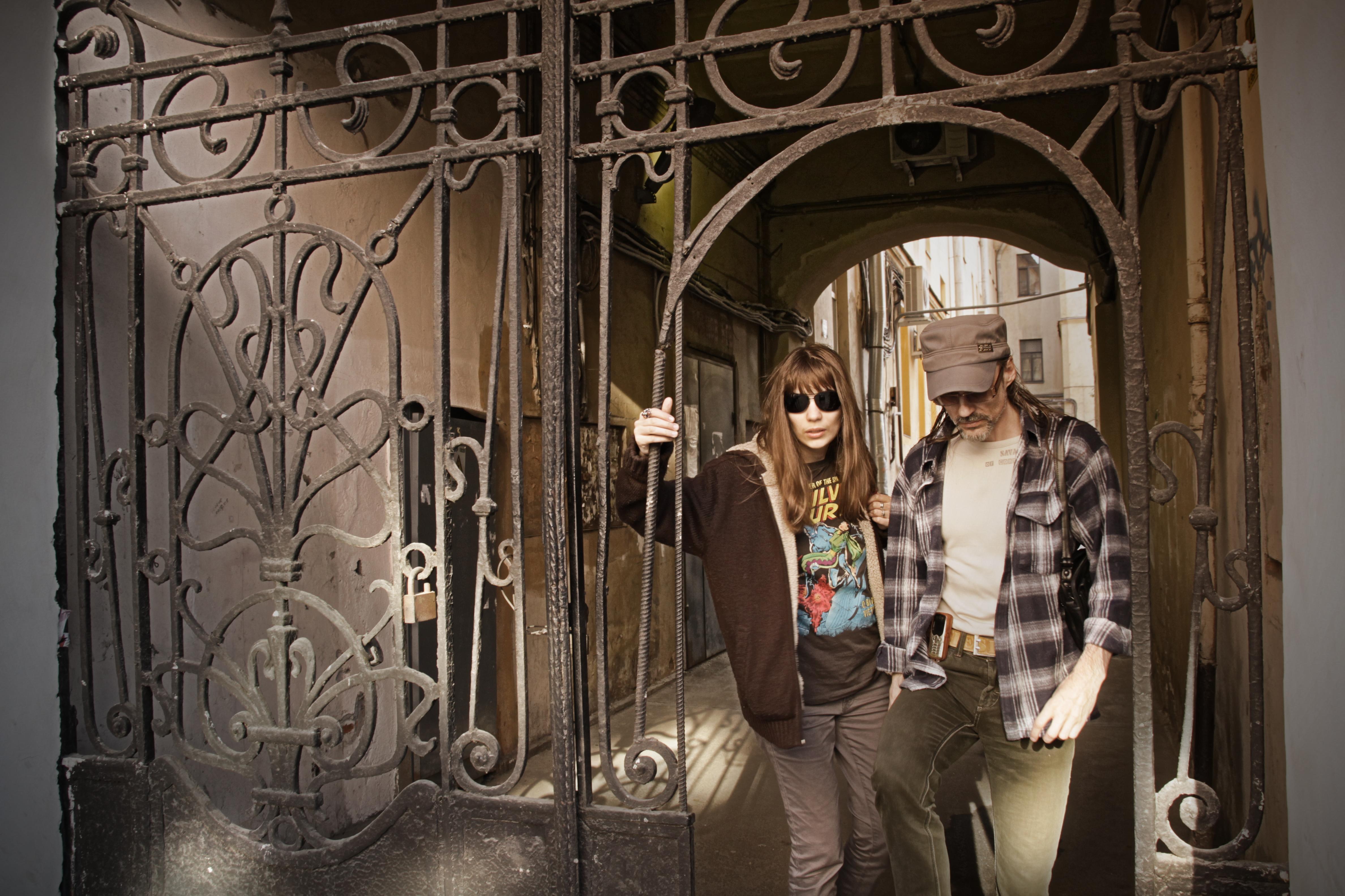 Пара выходит из кованных ворот в питерский двор.