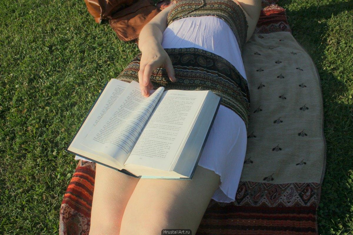 Фотография, девушка разлеглась на палантине в парке, уложив толстый фолиант фривольным образом себе на колени. Она листает страницы.