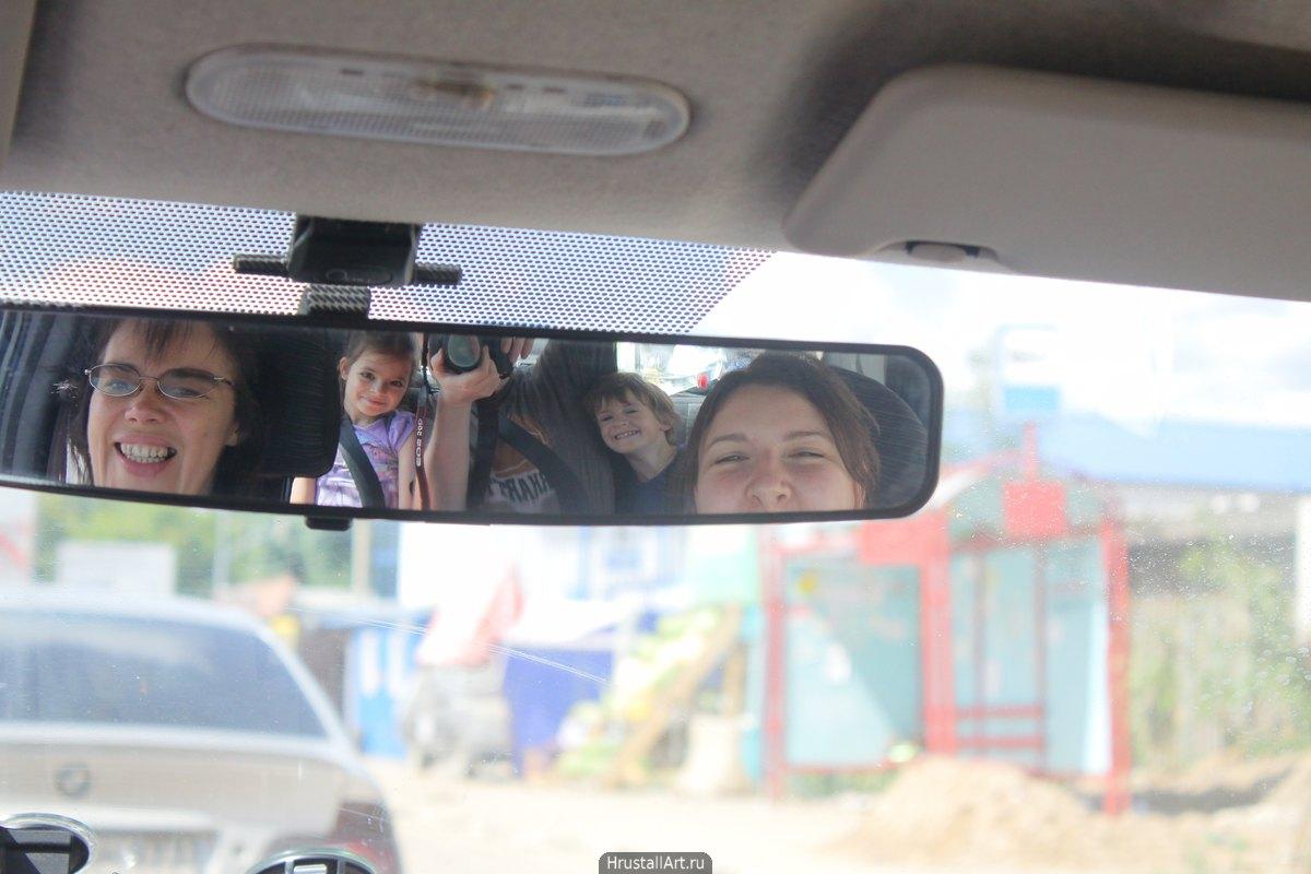 Фотография, в зеркале заднего вида отражаются все пассажиры авто, двое детей и трое взрослых, у компании хорошее настроение.