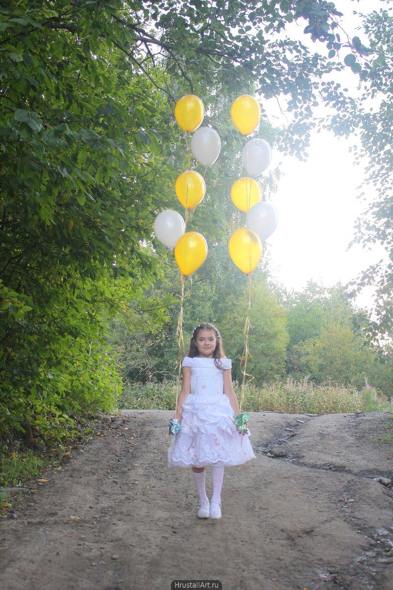 Фотография, девочка с праздничными шарами идёт по лесной дороге и протягивает шары зрителю.