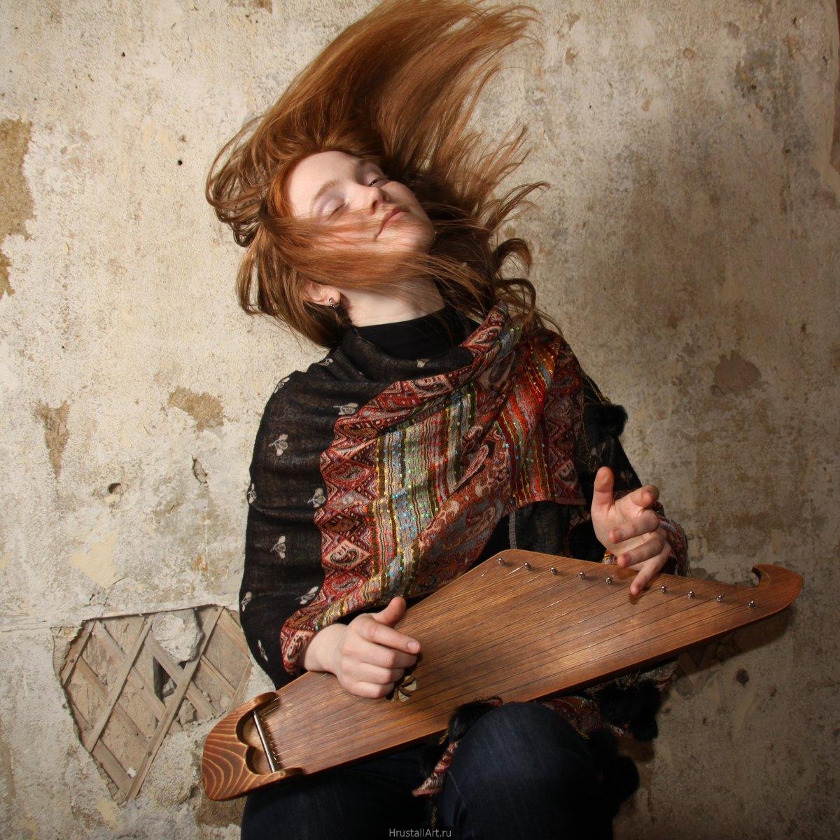 Фотография, молодая девушка играет на карельском кантеле (гуслях).