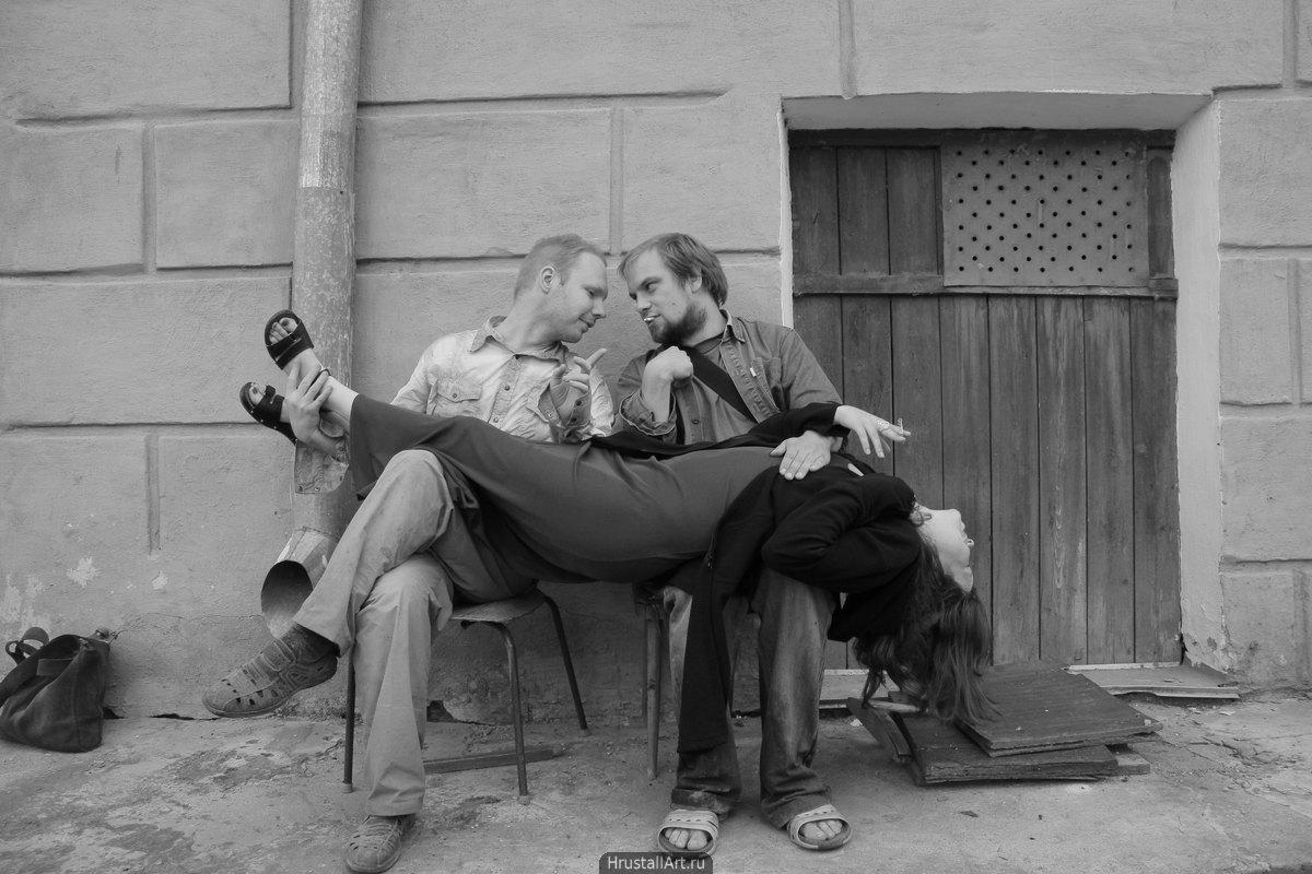Довольная девушка растянулась на коленях двоих парней, а они театрально беседуют.
