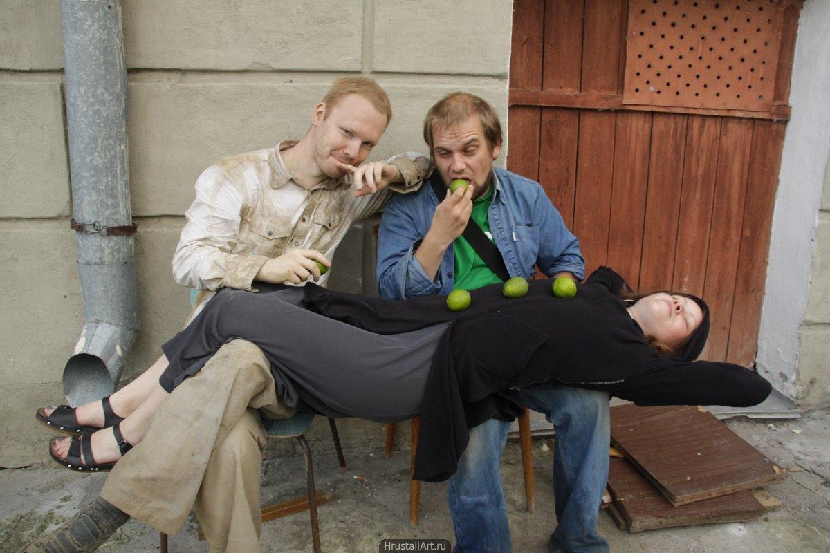 Девушка с пуговицами из лаймов растянулась на коленях двоих парней, один хитро смотрит на зрителя, другой, скислившись, кусает лайм.