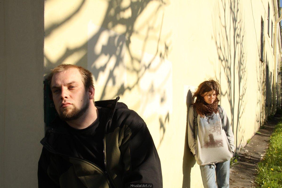 Фотография, пара молодых людей, на первом плане парень задумчиво или мечтательно смотрит вдаль, на заднем девушка с копной спутанных волос и полуулыбкой на лице. Тени от ветвей.