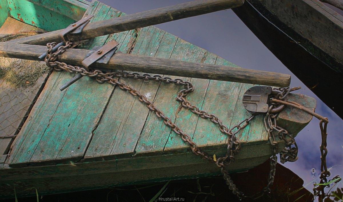 Фотография, старой, обветренной деревянной лодки прикованной к берегу ржавой цепью и замком.