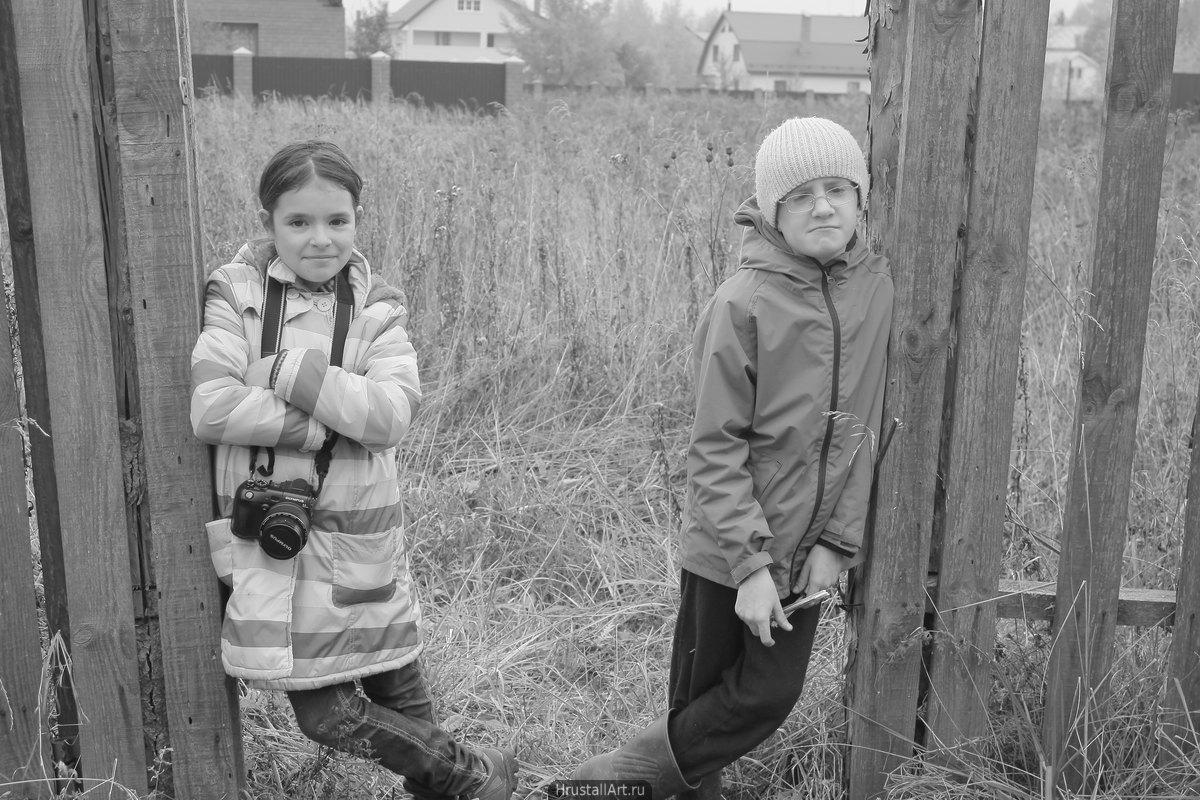 Двое детей стоят прислонившись к забору у заросшего пустыря.