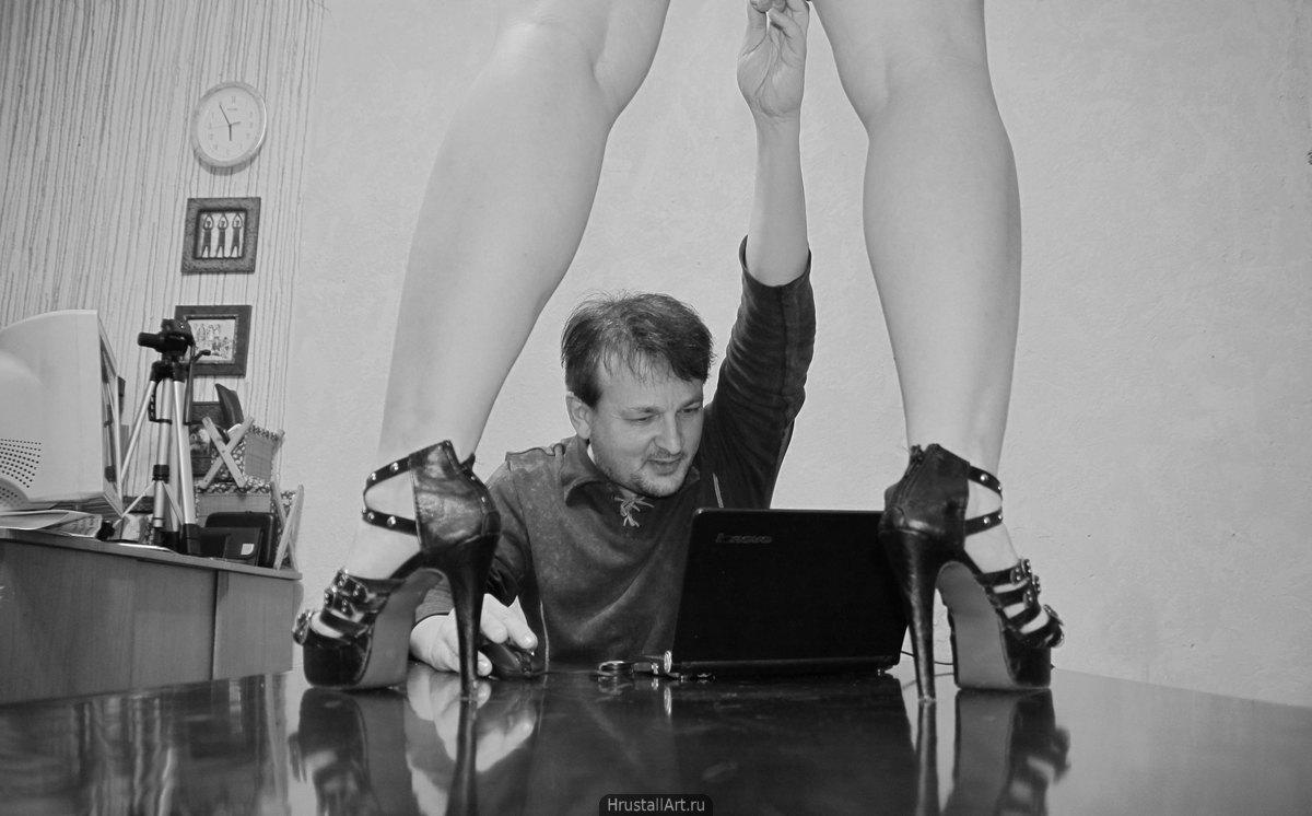 Фотография, ироническая сценка, мужчина не может оторваться от компьютера, в это время женщина в вызывающих каблуках встала на его стол и тащит его к себе.