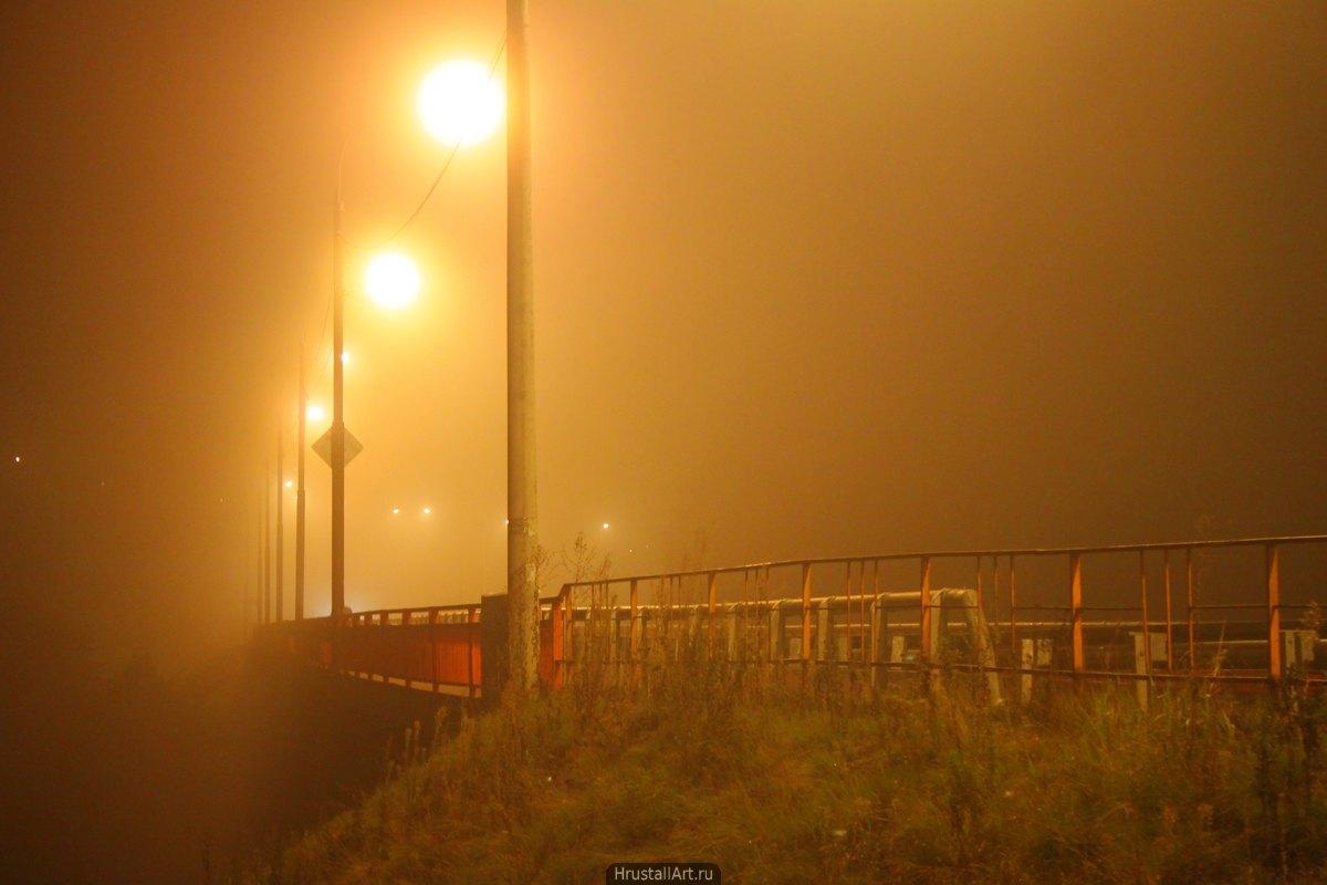 Фотография, мост в тумане освещается жёлтыми уличными фонарями.