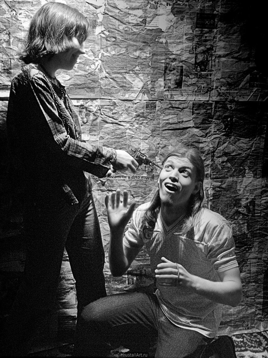 Фотография, грубоватая комическая сценка: улыбающаяся девушка приставила пистолет к виску коленопреклоненного парня, он театрально изображает ужас.