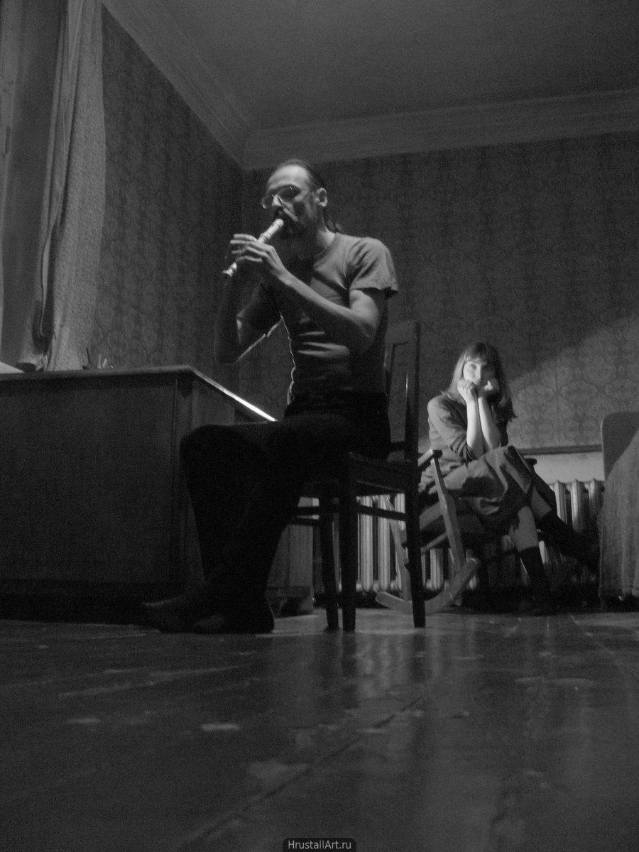 Фотография, в большой пустой комнате на стуле сидит худощавый мужчина и играет на флейте, на заднем плане в кресле-качале, подперев голову руками, его слушает молодая девушка.