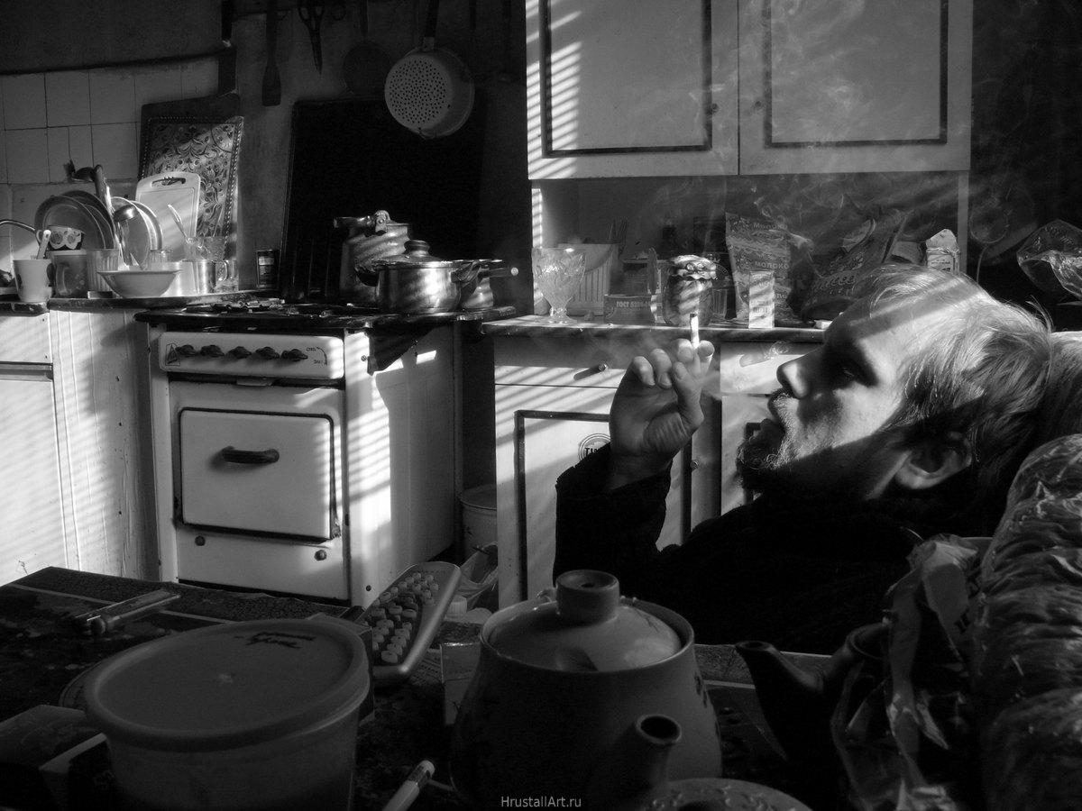 Фотография, на кухне советского вида с газовой плитой и вездесущим хаосом сидит парень с сигаретой, солнце освещает через жалюзи кухню косыми полосами света.
