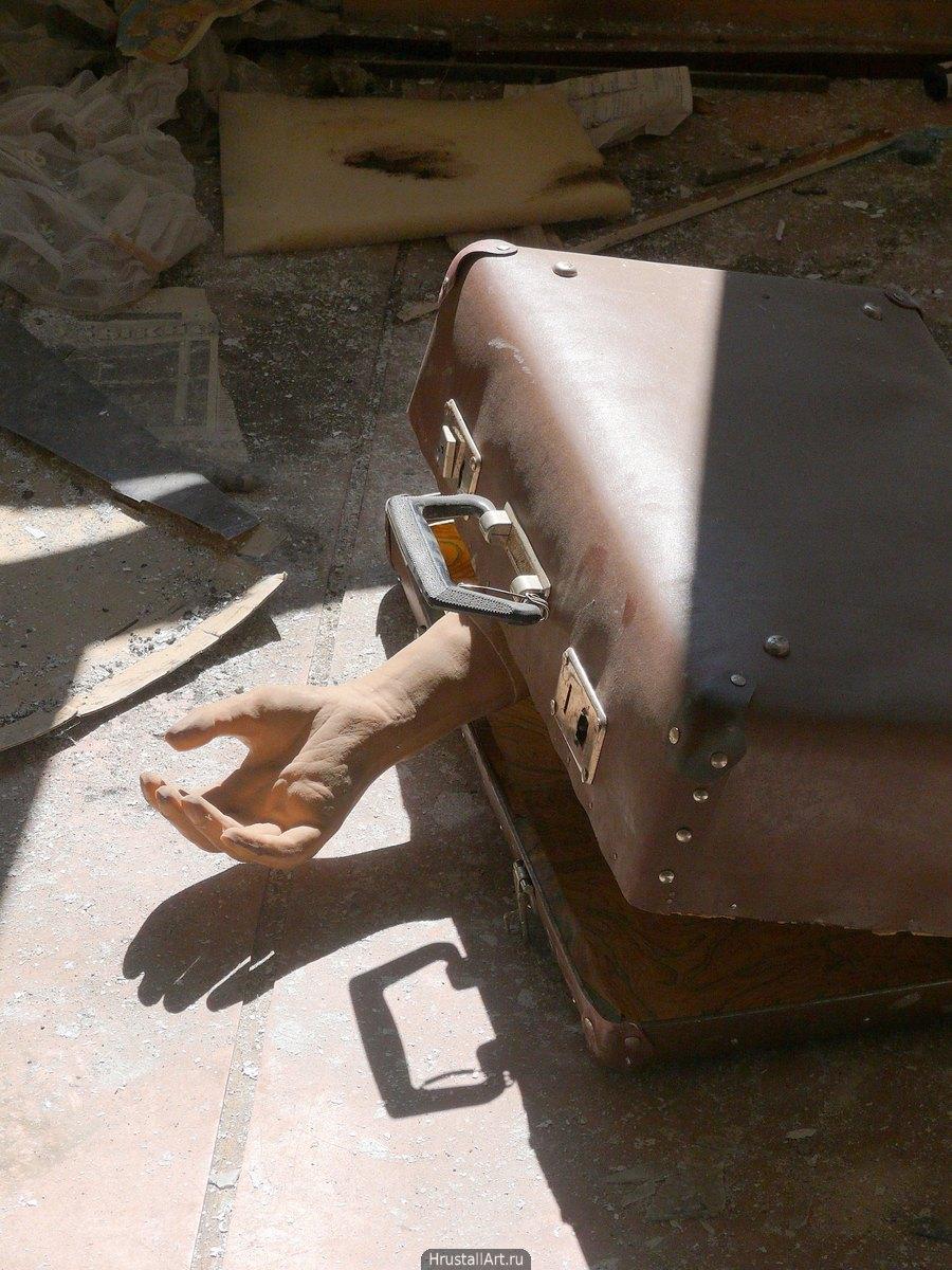 Фотография, на полу расселённого под снос дома лежит мусор и чемодан с выглядывающим из него протезом руки, протез очень реалистичен.