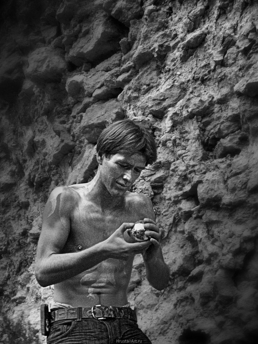 Фотография, молодой парень с крашеной серебренным акрилом кожей стоит на фоне каменной кладки с зеркальным шаром в руках.
