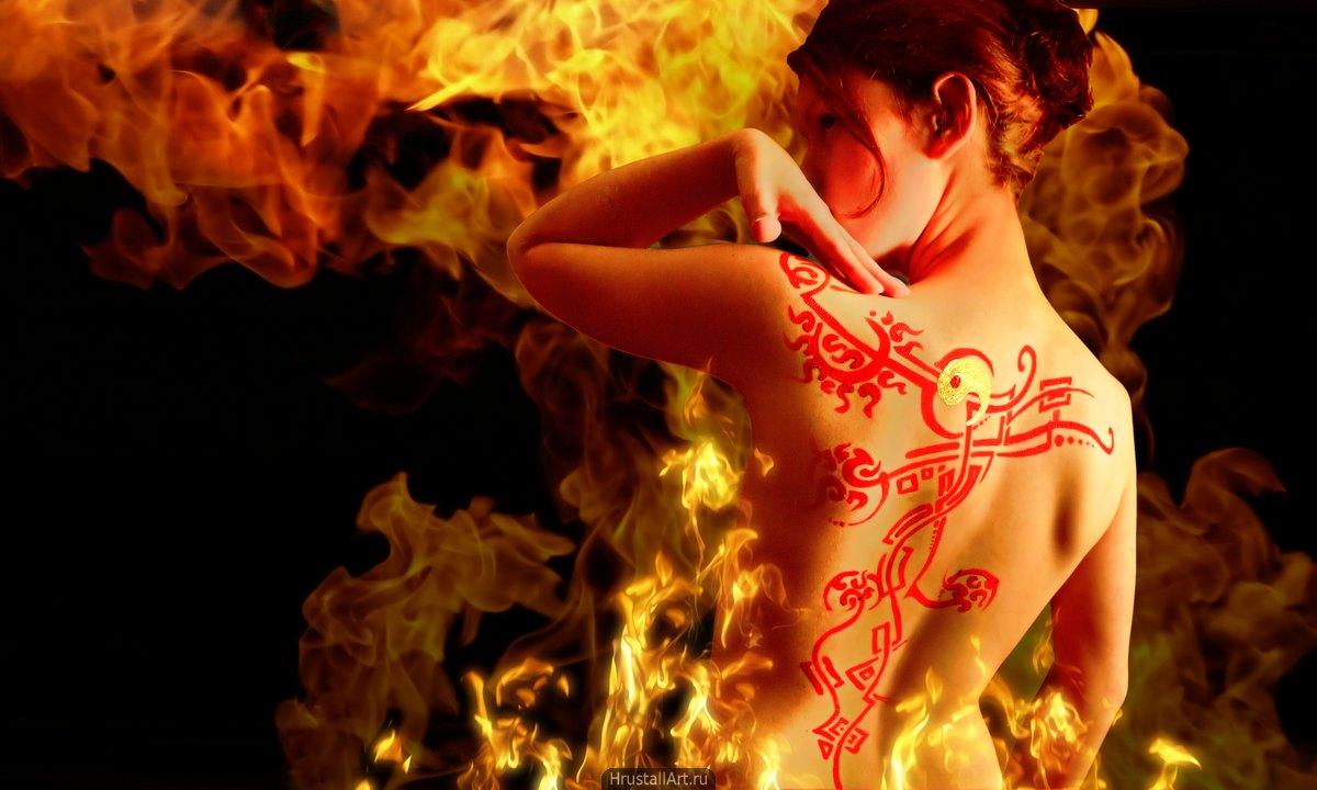 Фотография, девушка с красной росписью на спине полуобернулась к зрителю. Красная ткань и языки пламени.