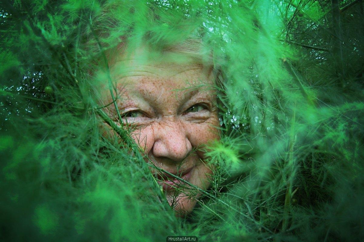 МамоФотография, сквозь пушистые и густые ветви декоративной травы выглядывает весёлое лицо женщины в возрасте.