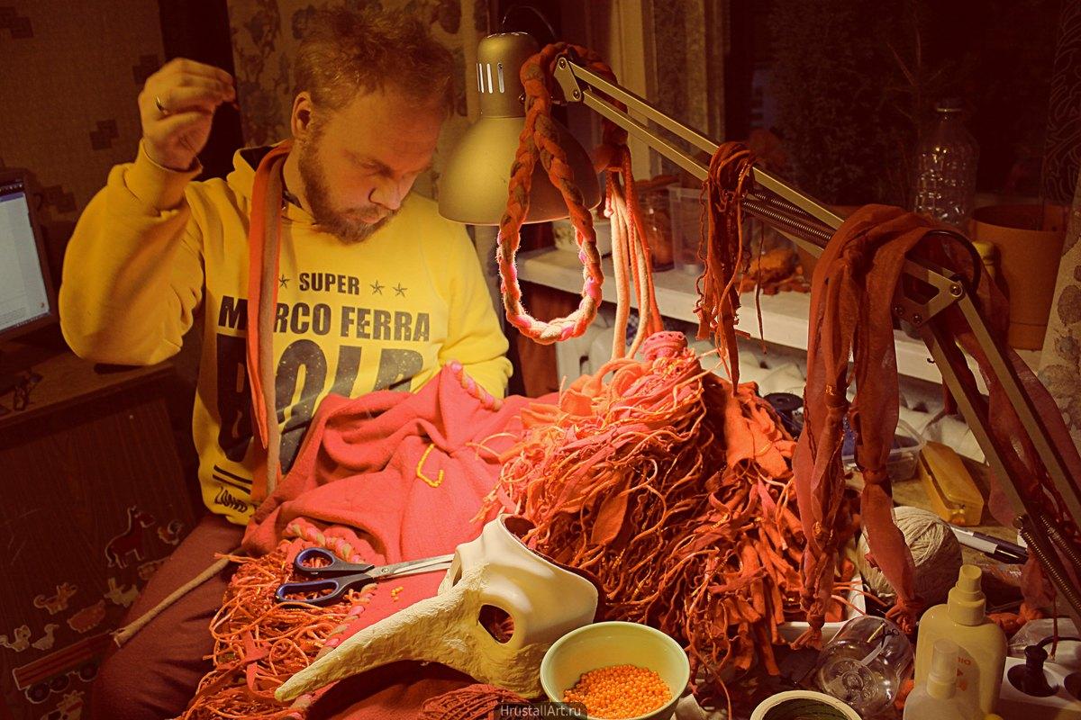 Мужчина за столом заваленным множеством ткани вышивает бисером.