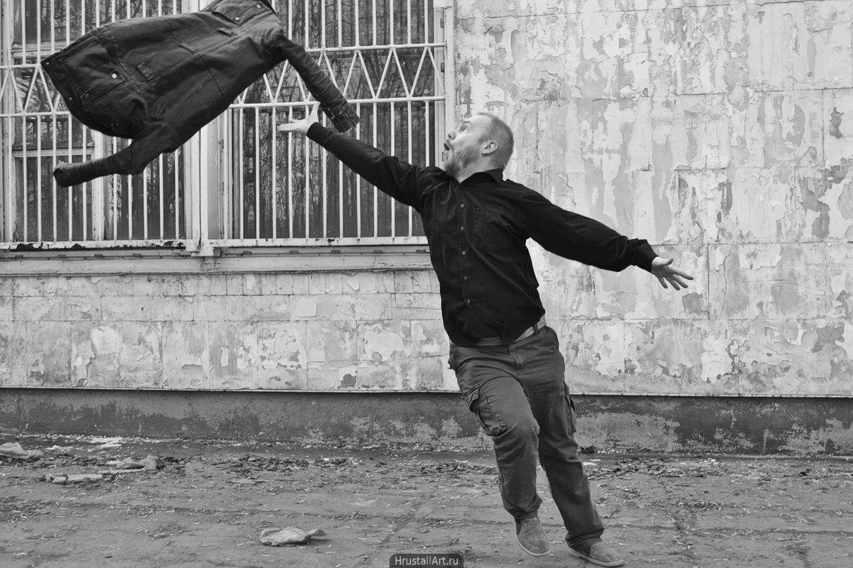 Ироничный кадр с летающей курткой и экспрессивным мужчиной.
