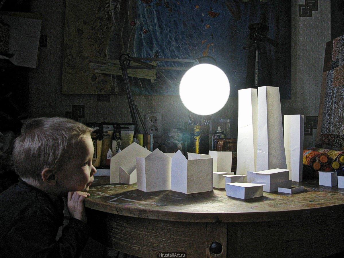 Игрушечный город из бумаги на столе, настольная лампа превратилась в солнце. Ребёнок разглядывает дома.