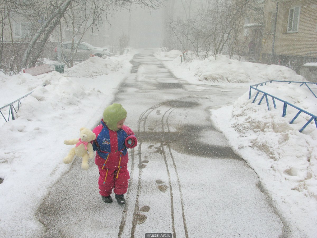 Зима, ребенок с плюшевым медведем гуляет по улице. Снегопад.