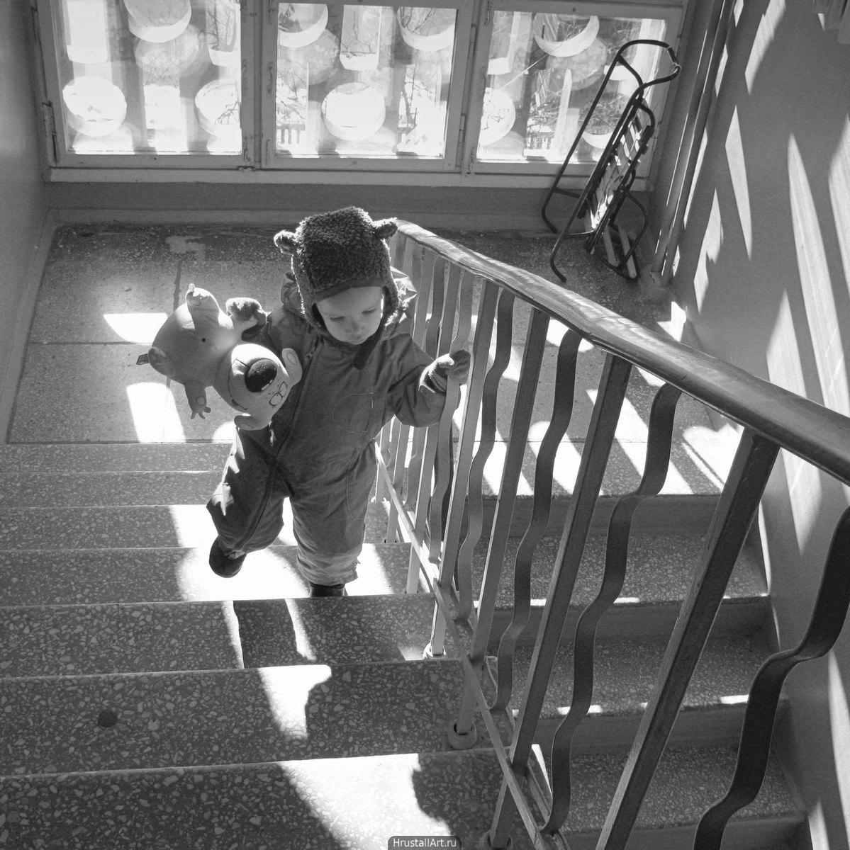 Лестничная клетка. ребенок с плюшевым мишкой возвращается с прогулки. Подъезд ярко освещён солнцем.