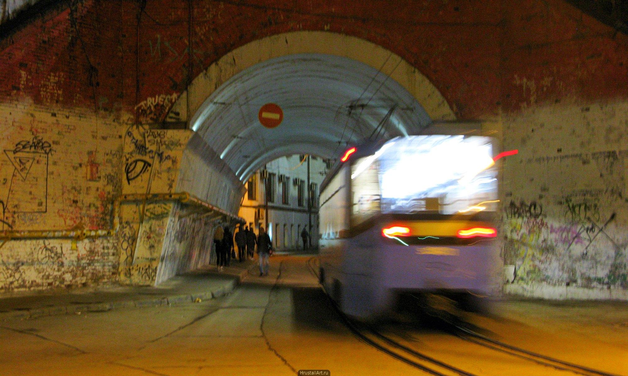 Ночной трамвай. Массивная арка проезда, вечерний свет, размытость трамвая от движения и длительной выдержки.