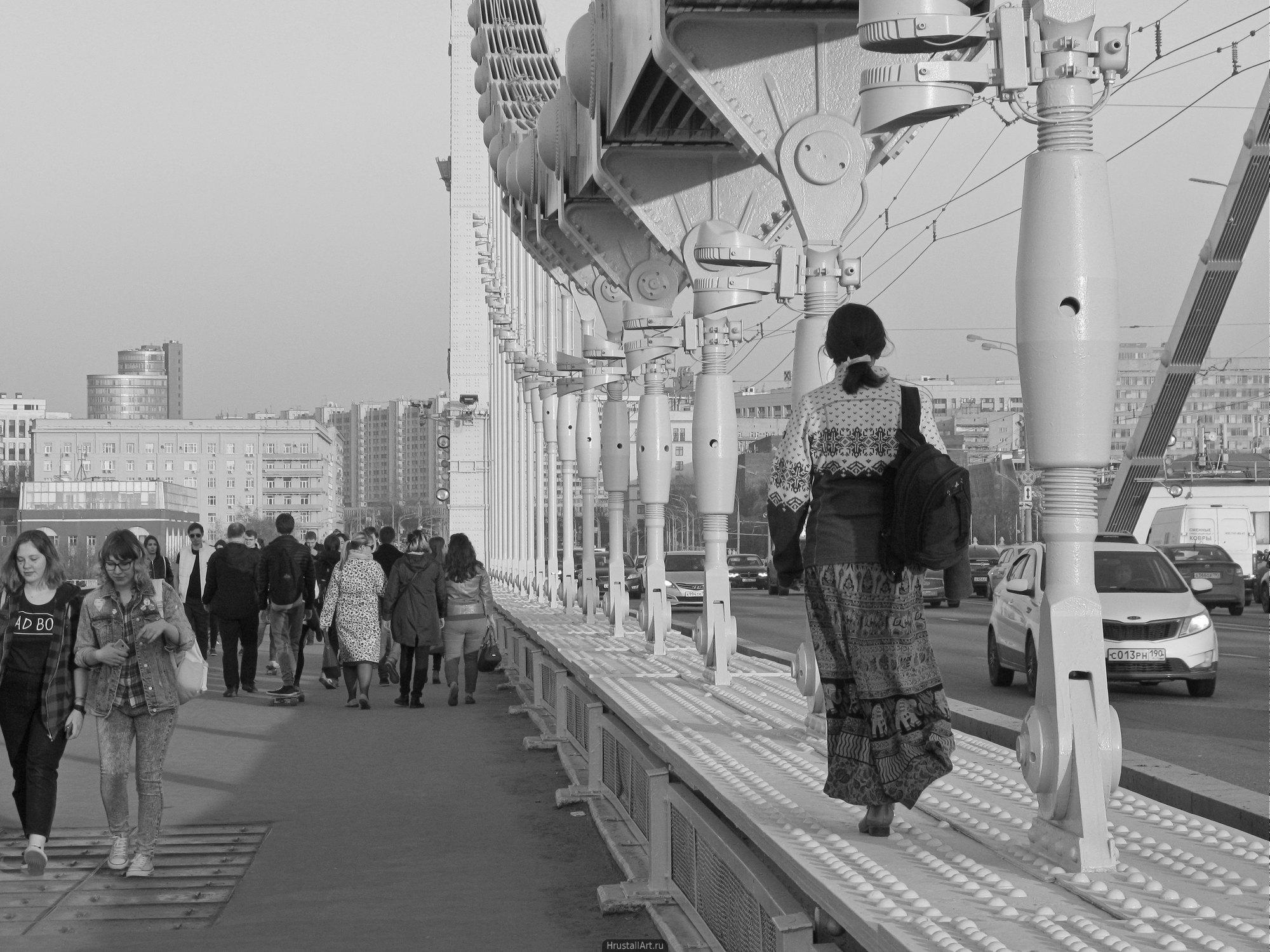 Девушка идет по конструкциям моста