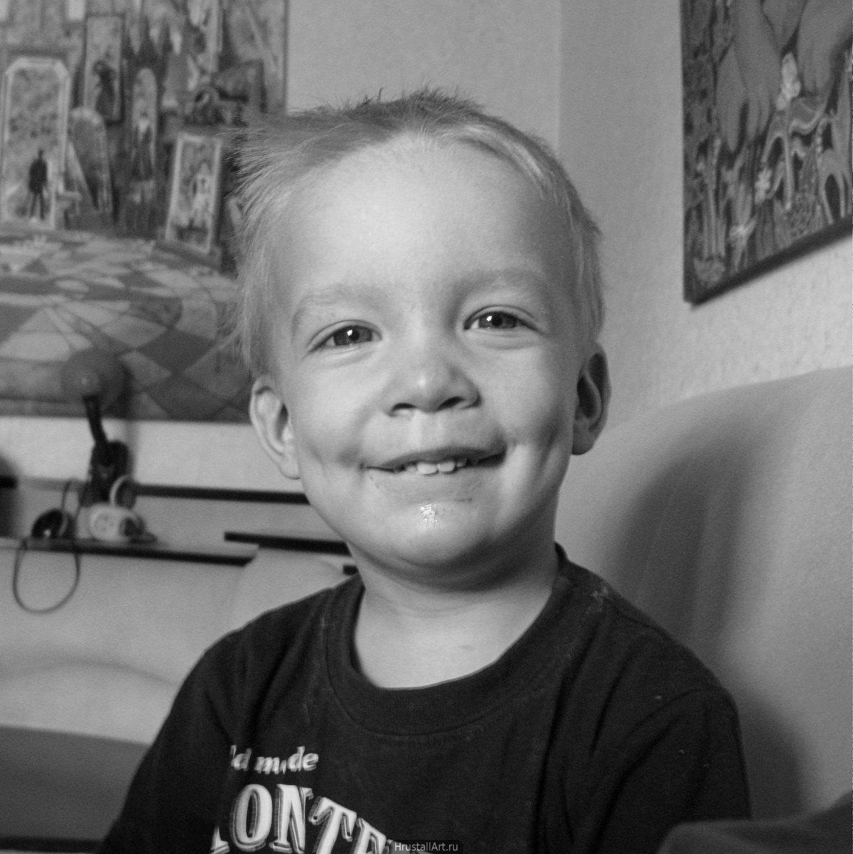 Мальчик хитро и нагло улыбается.