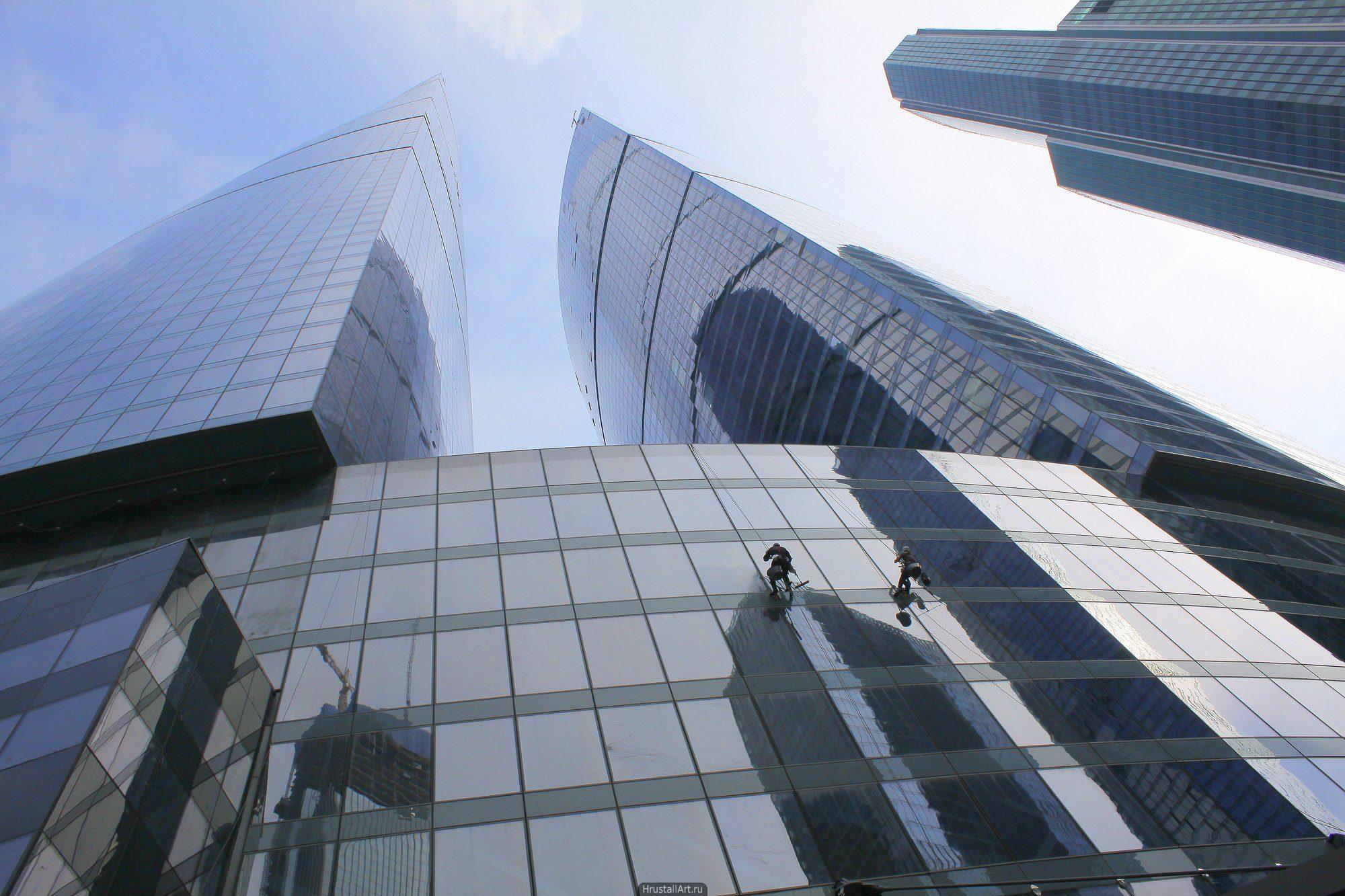 Масштаб человека на фоне стены небоскреба, промышленный альпинизм, мойщики зданий.