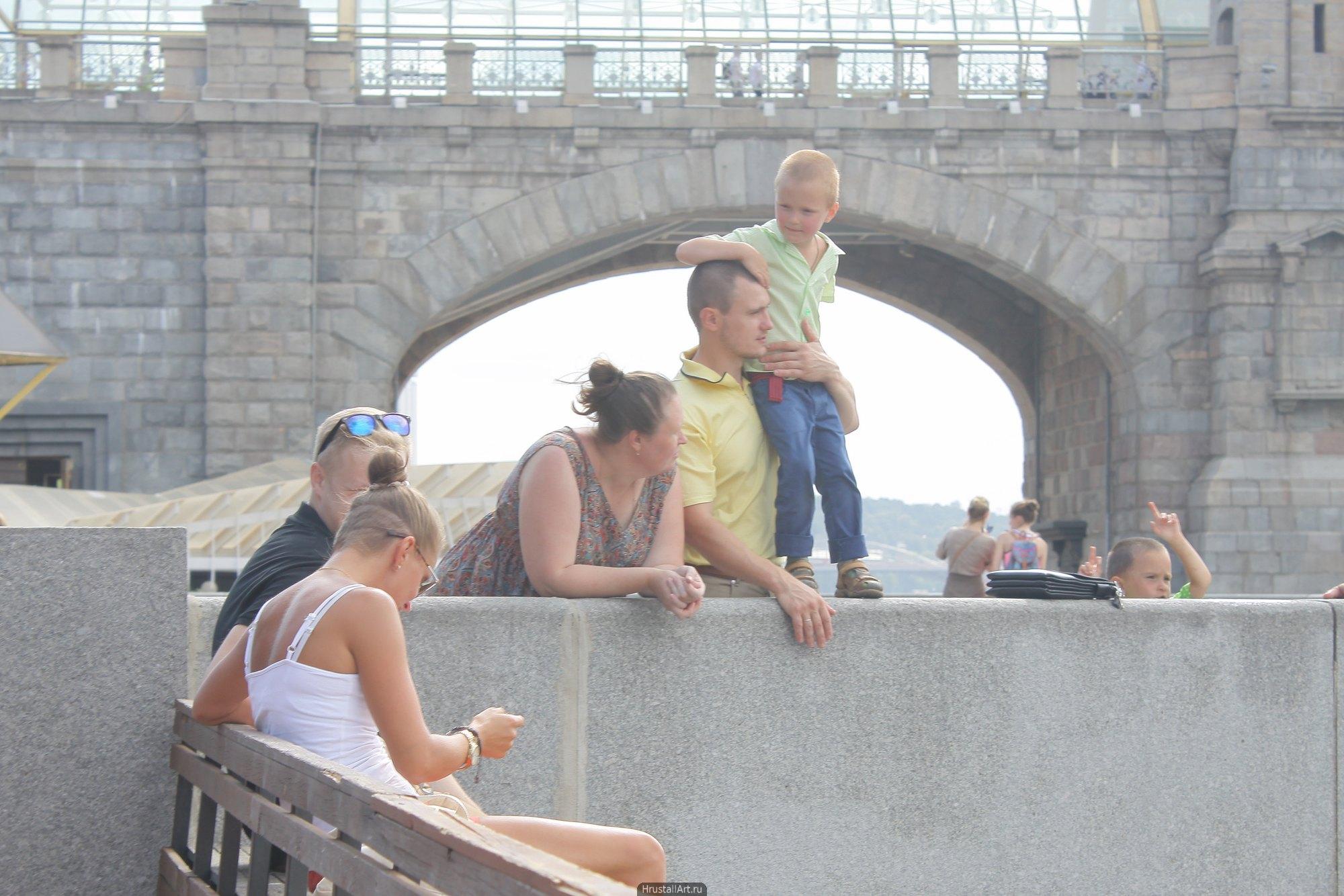 Семья с ребёнком и прочие прохожие залиты летним солнцем. На фоне — арка андреевского моста. Москва.