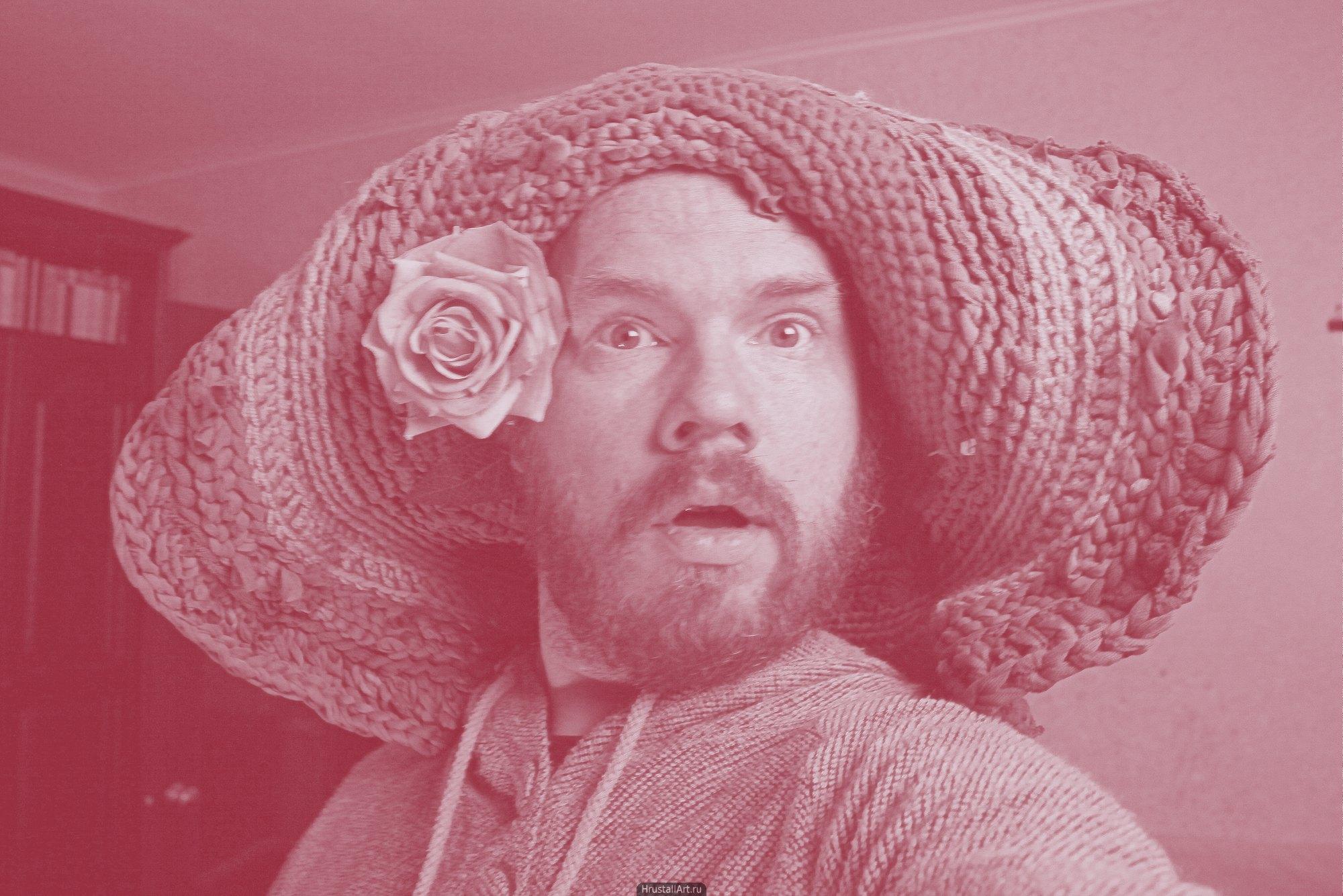 Мужчина с большой нелепой шапкой на голове и розой за ухом. Шапка напоминает вязаный из вторсырья ковер.