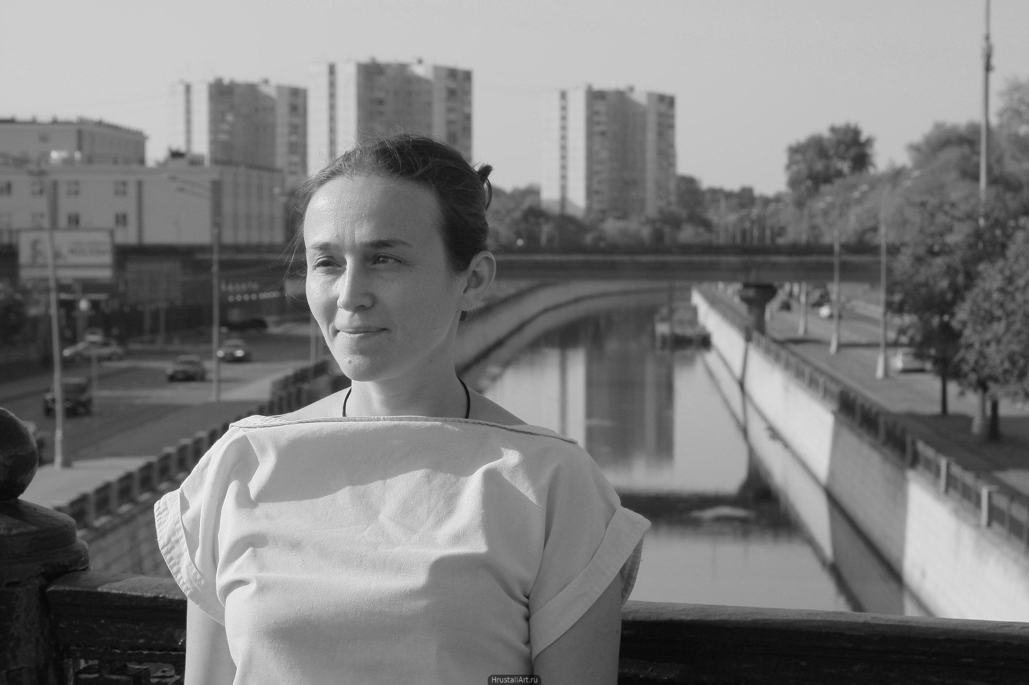 Девушка на фоне городского пейзажа с хитрым выражением лица.