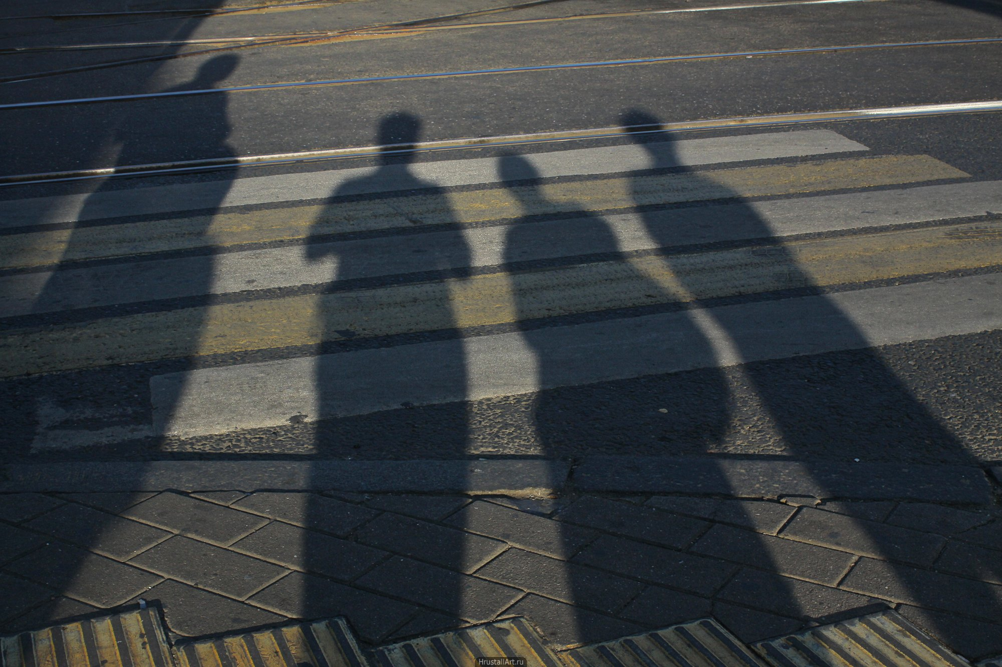 Тени людей на пешеходном переходе.